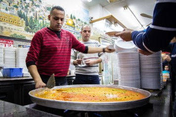 """""""Jerusalem kanafeh is a neon orange pastry with a crust of shredded phyllo dough or semolina filled with soft goat cheese and drenched in syrup. It is especially popular during Ramadan."""""""